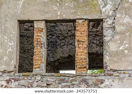Fragment of  brick  ruins with an empty window hole giving view to the inside of a ruined building