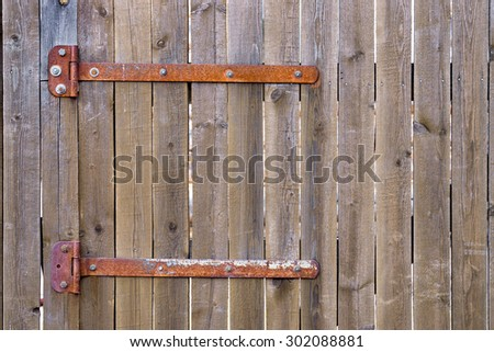 Fragment of closed wooden gate with rusty hinges - stock photo