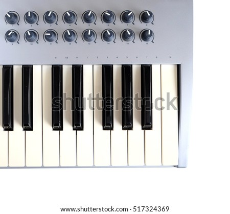 Fragment of electronic synthesizer keyboard with many control buttons isolated on white background top view closeup