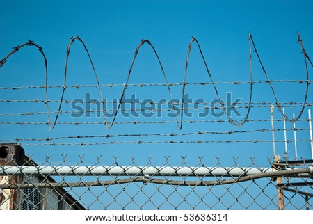 Fragment of fence of barbed wire curled in spiral on an industrial background - stock photo