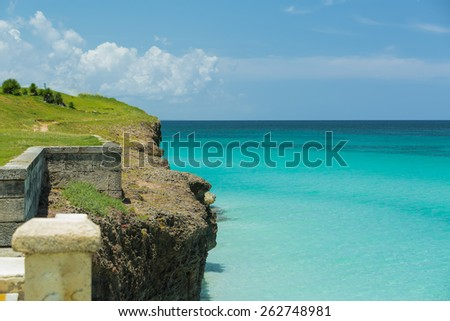 fragment of great amazing  tropical view of high green cliff over tranquil azure ocean against blue sky background - stock photo