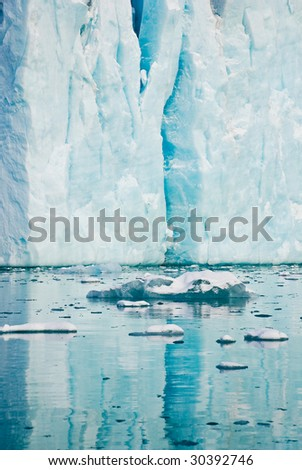 Fragment of iceberg on Spitsbergen island reflecting in water - stock photo