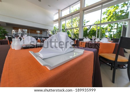 Fragment of interior of a restaurant and banquet table with napkin - stock photo