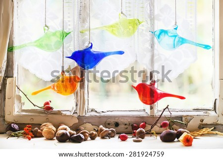 Fragment of interior on old windowsill with autumn berries, nuts and set of glass birds. See series - stock photo