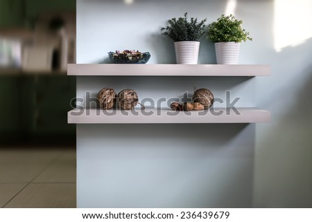 Fragment of interior. Wall with two white shelves, decorated with different objects. - stock photo