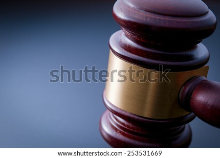 Fragment of judicial hammer on a blue background - stock photo