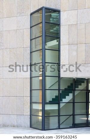 Fragment of modern building with interior staircase behind the glass - stock photo