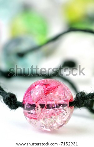 Fragment of Necklace with coloured Beads on a white background. Soft focus. - stock photo