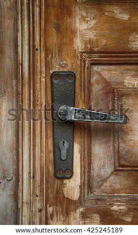 fragment of old door with a keyhole and door handle