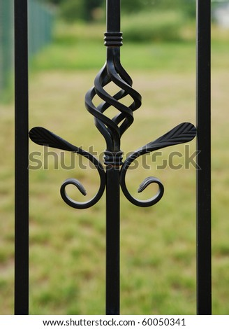 Fragment of old iron fence, green grass. - stock photo