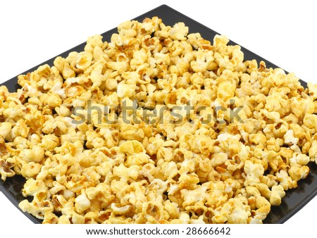 Fragment of plate with fresh caramel popcorn. Isolated - stock photo