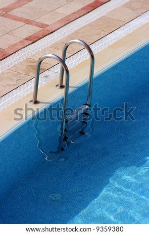 Fragment of pool with a ladder and transparent water