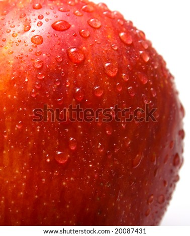 Fragment of red apple covered by water drops on the white background. Isolated. Shallow DOF.