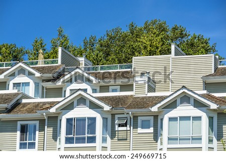 Fragment of residential buildings with blue sky background. British Columbia, Canada. - stock photo