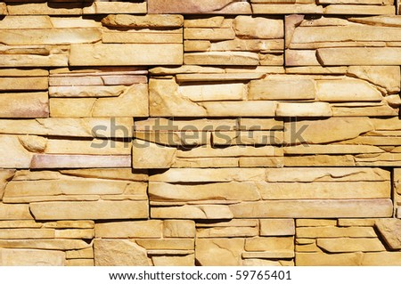 Fragment of rough wall made of yellowish colored flat stones - stock photo