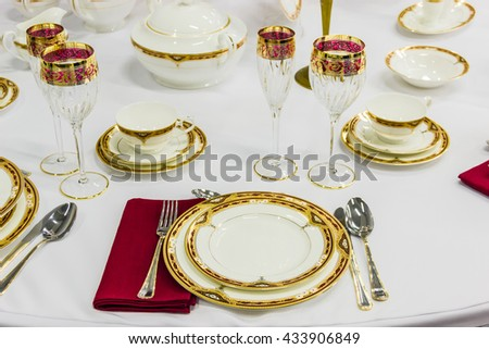 Fragment of table setting with tableware, cutlery and a glass, decorated with golden and red ornament
