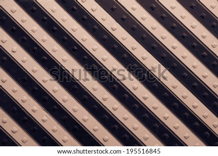 fragment of the ancient riveted panel from the painted wooden boards with black brown slanting striped pattern - stock photo