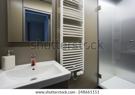 Fragment of the bathroom interior with a wash basin and heated towel rail. - stock photo