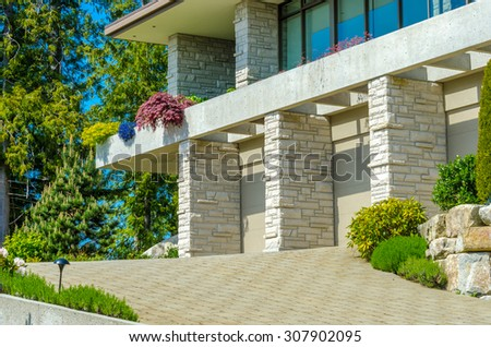 Fragment of the big custom made luxury modern house with nicely paved driveway in the suburbs of Vancouver, Canada. - stock photo