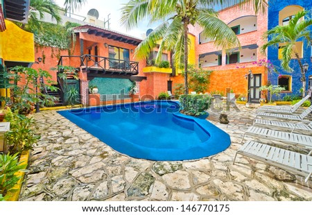 Fragment of the caribbean mexican building in traditional style. Colorful inner court, yard, plaza with brightly colored walls and swimming pool. - stock photo