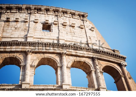 Fragment of the Coliseum against the blue sky. Italy