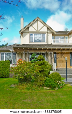 Fragment of the custom made luxury house with nicely trimmed and landscaped front yard in suburbs of Vancouver, Canada. - stock photo
