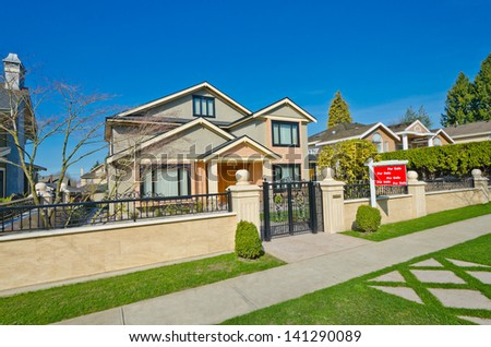 Fragment of the Luxury custom made house behind iron gates with long doorway at sunny day in Vancouver, Canada. - stock photo