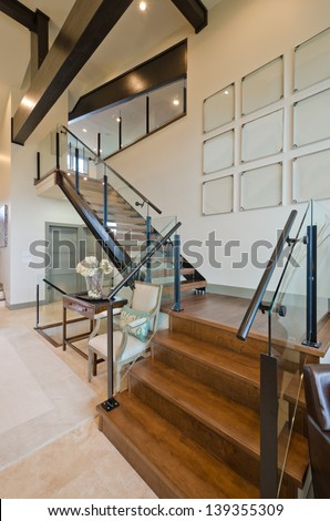 Fragment of the luxury spacious modern room with the stairs to the upper level. Interior design. Vertical.
