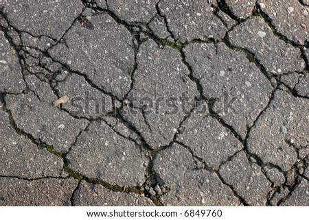 Fragment of the old cracked asphalt road - stock photo