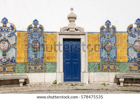 Fragment of the old historical building with the blue door and azulejos (painted tin-glazed ceramic tilework) located in Alcantara area, Lisbon, Portugal.