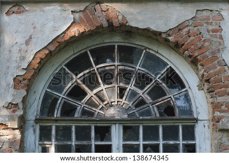 fragment of the old round window with broken windows - stock photo