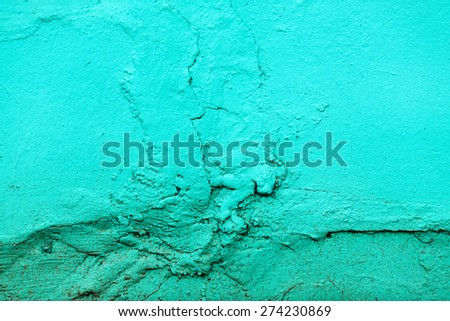 Fragment of the old wall, painted bright turquoise paint, cracked over time. - stock photo