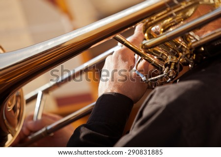 Fragment of the trombone in the hands of the musician - stock photo