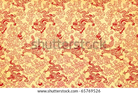 Fragment of yellow chinese silk with red dragons and flowers - stock photo