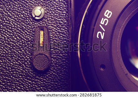 Fragment old film DSLR camera with lens. Lens and camera self-timer button. Front view. Macro. Vintage photo. Toning. - stock photo