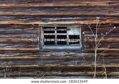 Fragment old wooden log house with a window without glass in russian village