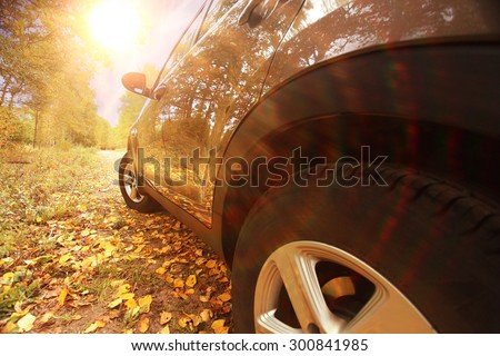fragment the car in the autumn landscape - stock photo