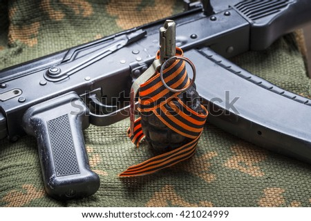 Fragmentation grenade, and Kalashnikov rifle, with St. George ri - stock photo