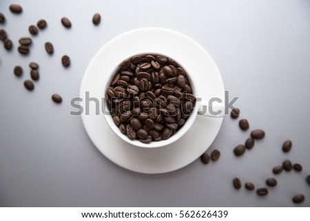 Fragrant coffee beans in a white cup.