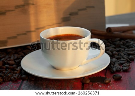 Fragrant coffee in a cup standing on a wooden table in the coffee beans - stock photo
