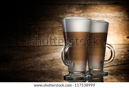 Fragrant coffee latte in glass cups and cinnamon on wooden table on brown background - stock photo