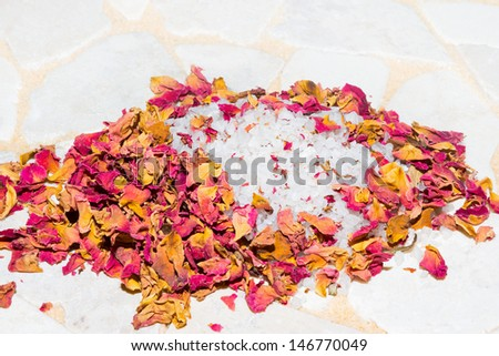 Fragrant dried pink rose petals with coarse crystallized bath salts for a relaxing aromatic bath promoting rejuvenation and wellbeing in a spa or health resort - stock photo