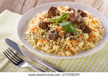 Fragrant pilaf with meat and vegetables close up on a plate