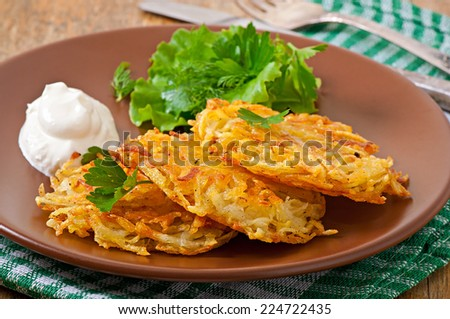Fragrant potato pancakes with sour cream and herbs - stock photo