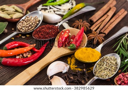 Fragrant spices in spoons on wooden background.
