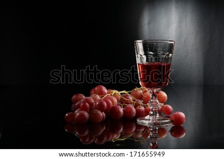 Fragrant tasty grape wine in a beautiful glass and a cluster of fresh ripe sweet juicy pink grapes - stock photo