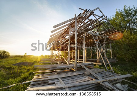 frame building under construction at sunset - stock photo