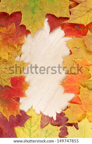 Frame composed of colorful autumn leaves on wooden background texture - stock photo
