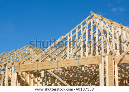 Frame construction of a truss roof with hurricane tie down clips for a house.