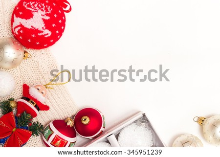 frame for text of Christmas toys on green fir branch namely big red ball with Christmas deer and the box with the new white balls and also red bow, garland and toy Santa Clause - stock photo